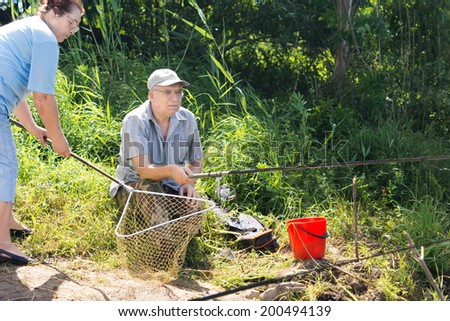 Couple fishing with the woman holding a net as she prepares to catch the fish that her husband is busy reeling in on his rod and line