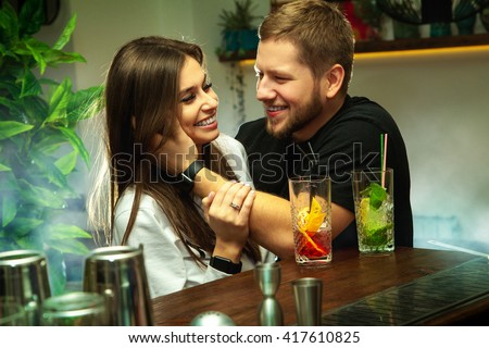 couple flirting at the bar with alcoholic cocktails. couple in love laughing at the bar - stock photo
