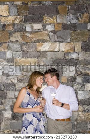 Couple flirting beside stone wall, holding glasses of white wine, smiling - stock photo