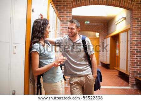 Couple flirting in a corridor while leaning on the lockers - stock photo