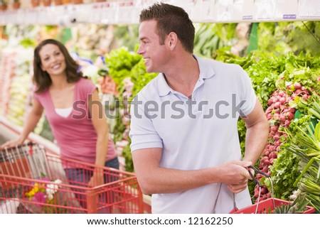 Couple flirting in supermarket aisle - stock photo