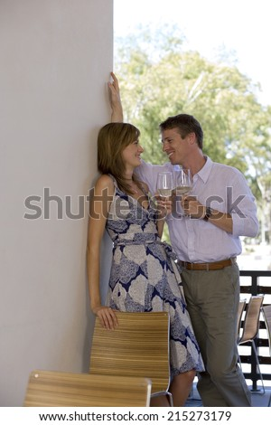 Couple flirting on balcony, holding glasses of white wine, smiling, side view - stock photo
