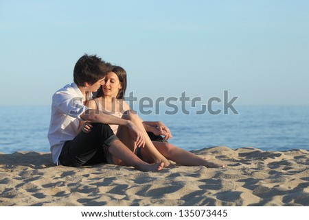 Couple flirting sitting on the sand of the beach with the sea in the background - stock photo