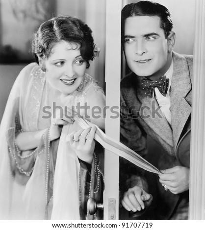Couple flirting through a slightly open door - stock photo