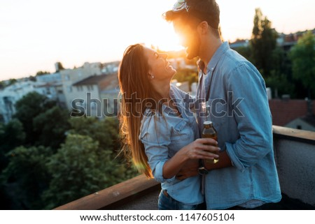 Couple flirting while having a drink on rooftop terrasse