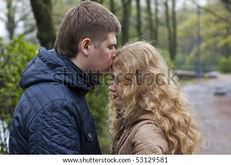 couple forehead kissing outdoors in spring - stock photo