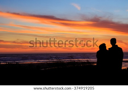 Couple from the back at sunset on a beach in Oregon. - stock photo