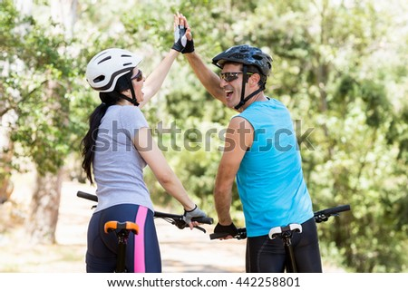 Couple from the back clapping hands each other on their bikes - stock photo