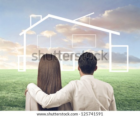 Couple, from the back, on a large lawn watching a house drawn on a large lawn - stock photo