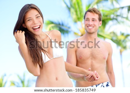 Couple fun at beach holding hands in bikini and swimwear smiling happy on honeymoon travel holidays in tropical paradise with palm trees. Happy interracial couple, Asian woman, Caucasian man. - stock photo
