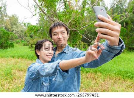 Couple fun taking self-portrait picture photos with mobile smart phone - stock photo