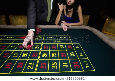 Couple gambling at roulette table - stock photo