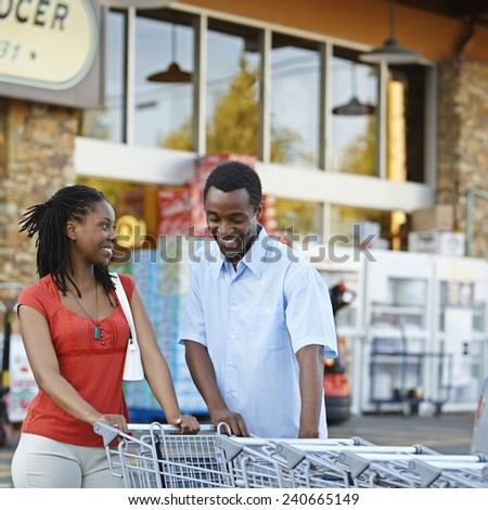 Couple Getting Grocery Cart - stock photo