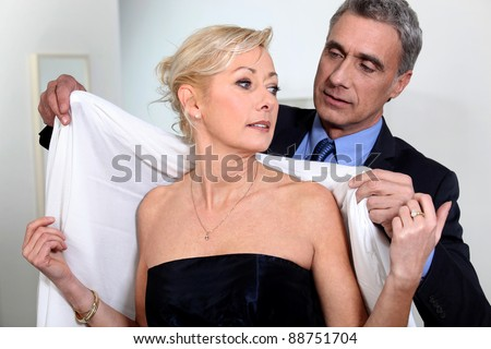Couple getting ready to go out - stock photo