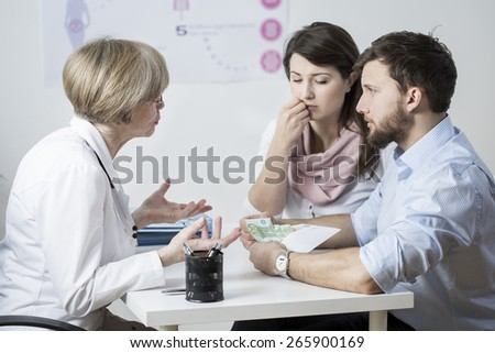 Couple giving a bribe to speed up their treatment - stock photo