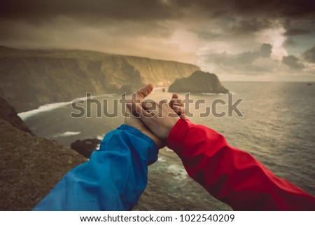 Couple giving hands with a beautiful landscape as background