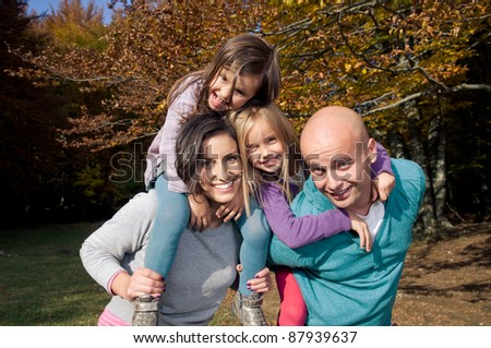 Couple giving two young children piggyback rides - stock photo