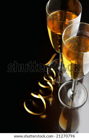 Couple glasses of champagne with gold streamer and space for your own text on left - stock photo
