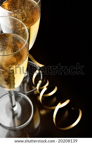 Couple glasses of champagne with gold streamer and space for your own text on right - stock photo
