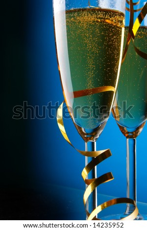 Couple glasses of champagne with gold streamer over blue background - stock photo