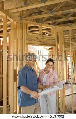 Couple go over home building plans at a construction site. Vertical shot. - stock photo
