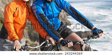 couple going on a bike ride on the beach  - stock photo