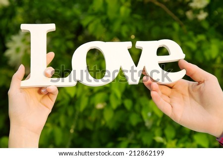 Couple hands holding love word in natural environment  - stock photo