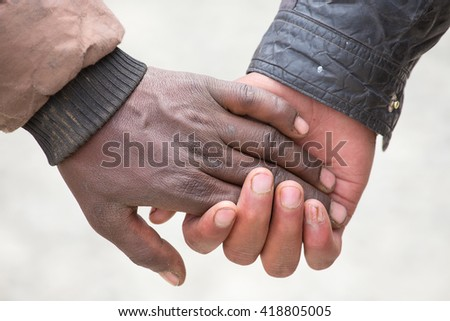Couple hands on the street in India, close up. In India, it is normal to go to men holding each other by the hand