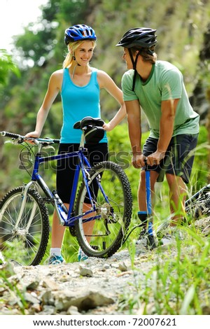 Couple have a flat tyre with mountain bike outdoor in the wilderness - stock photo