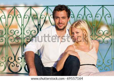 Couple having a city break in summer sitting on a bridge over a river in the evening light