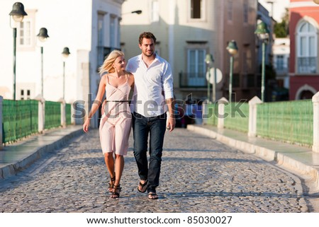 Couple having a city break in summer walking on a bridge over a river in the evening light - stock photo