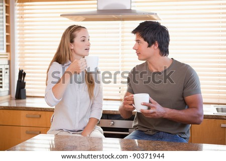 Couple having a cup of tea in their kitchen - stock photo