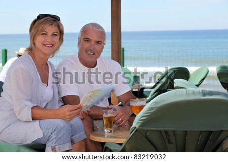 Couple having a drink on holiday - stock photo