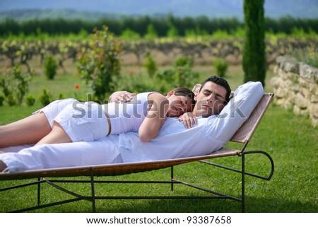 Couple having a nap on sun lounger - stock photo