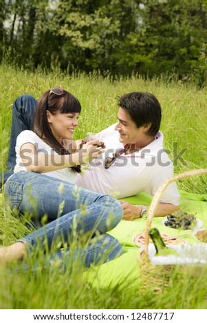 couple having a picnic in a park, smiling - stock photo