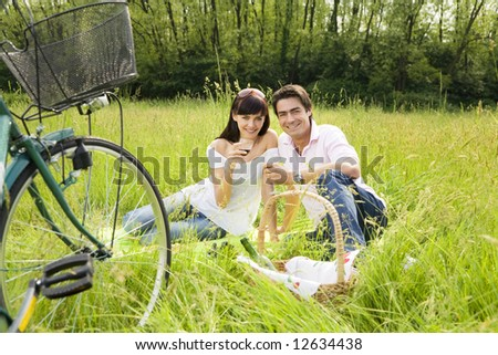 couple having a picnic in a park, smiling and looking at the camera - stock photo