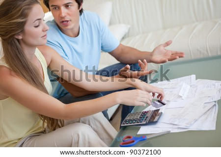 Couple having an argument about their bills in their living room - stock photo