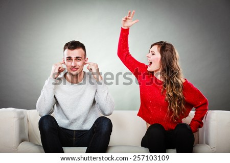 couple having argument - conflict, bad relationships. Angry fury woman screaming man closes his ears. - stock photo