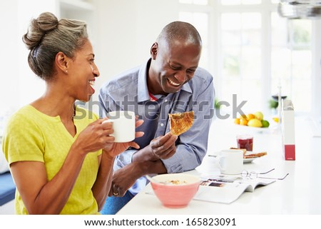 Couple Having Breakfast And Reading Magazine In Kitchen - stock photo
