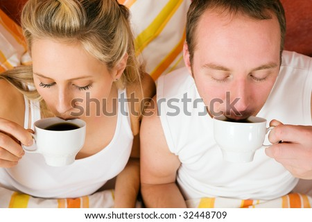 Couple having breakfast in bed in the morning - stock photo