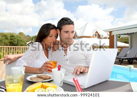 Couple having breakfast outside in front of laptop