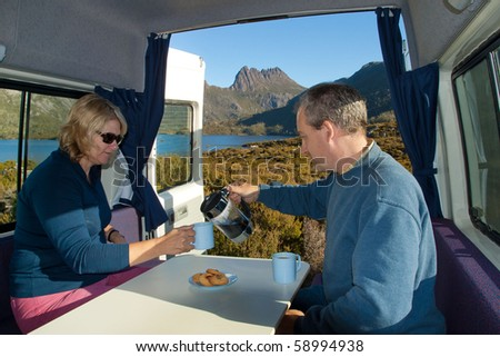 couple having coffee in camper van at Cradle Mountain - stock photo