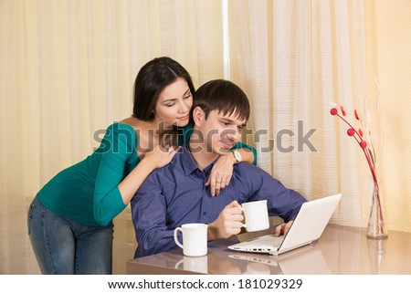 Couple having coffee while using a laptop in their kitchen