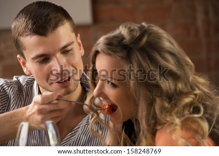 Couple having dinner in a restaurant - man feeding his woman and both having fun - stock photo