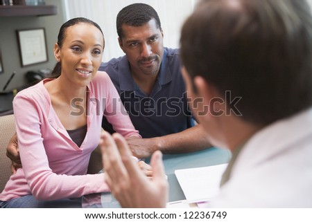 Couple having discussion with doctor in IVF clinic sitting at desk - stock photo