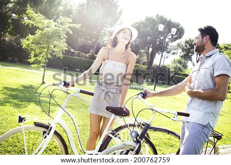couple having fun by bike on holiday to the lake in Italy - stock photo