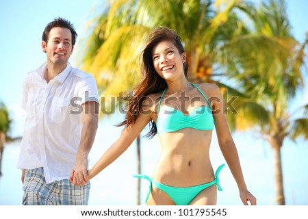 Couple having fun on beach. Happy young interracial couple running on beach during summer vacation on tropical resort. Asian woman, Caucasian man smiling happy in Varadero, Cuba - stock photo