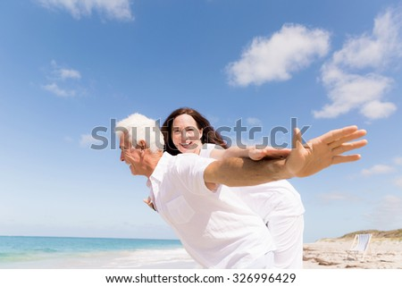 Couple having fun on the beach - stock photo