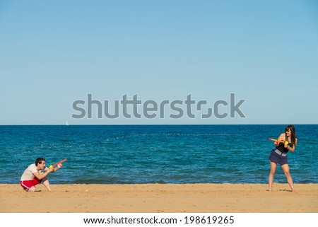 Couple having fun on the beach with a water gun fight - stock photo