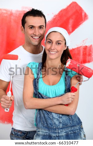 Couple having fun painting their new house - stock photo